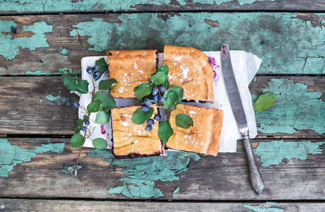 Blueberry pie pieces over a rustic painted wooden surface