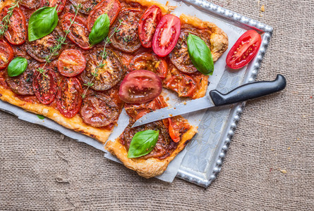 Tomato open pie with fresh basil and thyme  over a sackcloth sur