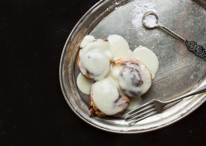 Cinnamon rolls with cream icing and sugar powder on a metal dish