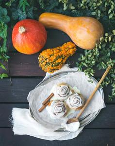 Cinnamon pumpkin buns with creamy cheese icing and ripe pumpkins