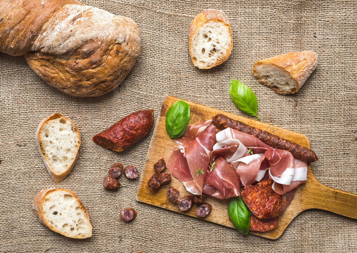 Meat plate on rustic wood board over a rough sackcloth backgroun