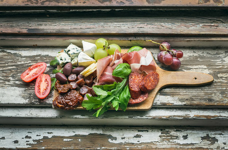 Meat appetizers selection on the old painted wood background