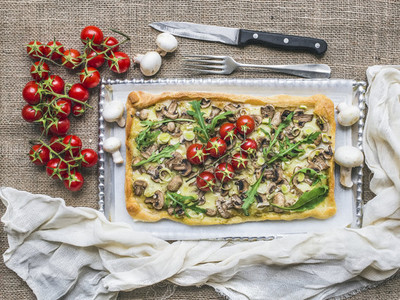 Rustic square mushroom pizza with fresh arugula and cherry tomat