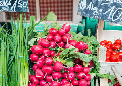 Garden radish and spring onions on a market stall