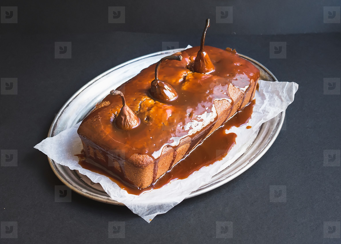 Spicy pear cake with caramel topping on a silver dish on a dark