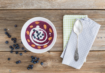 Blueberry and cream soup with almond over a rough wooden surface