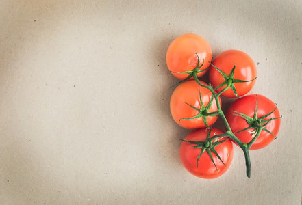 Bunch of fresh ripe red tomatoes over a craft paper background w