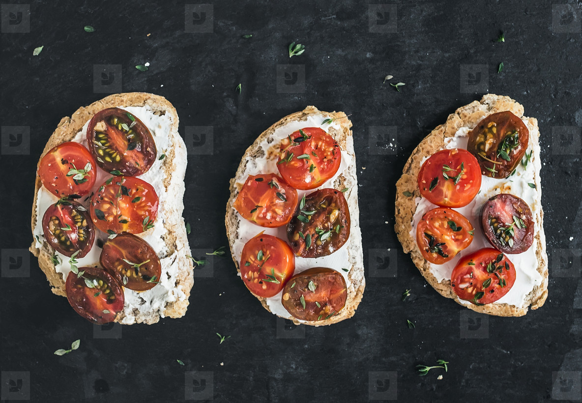 Ricotta and cherry tomato sandwiches with fresh thyme over a dar