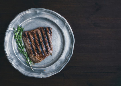 Beef steak with rosemary on a vintage metal plate over a dark wo