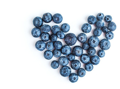 Heart sign made of fresh blueberries on a white background