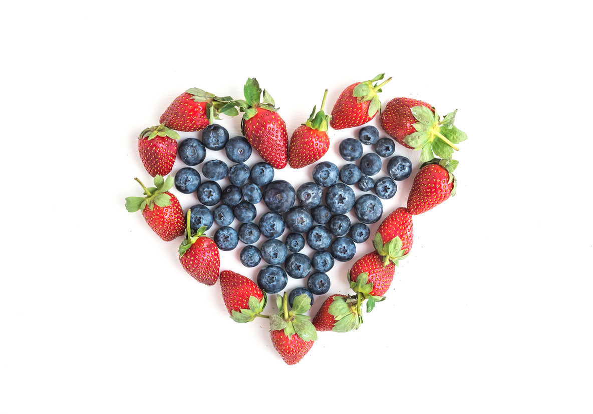 Heart sign made of fresh blueberries and strawberries on a white