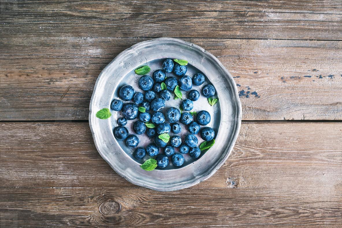 Old vintage metal plate full of fresh ripe blueberries