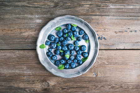 Old vintage metal plate full of fresh ripe blueberries