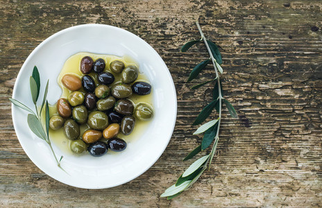 Plate of Mediterranean olives in oil with tree branch
