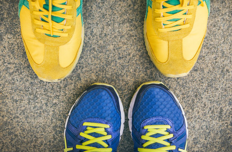 Two pairs of bright sport shoes standing in front of each other
