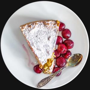 A piece of custard cherry pie on a white ceramic dessert plate