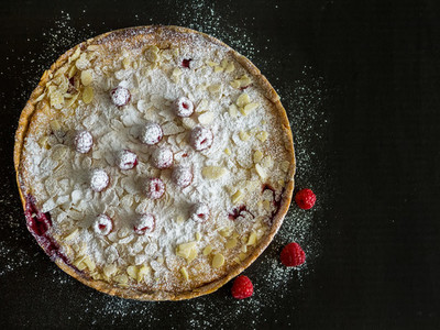 Raspberry and mascarpone pie on a black background