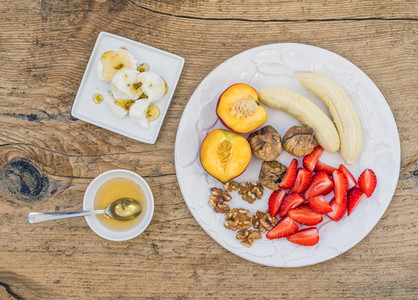 Breakfast set with fresh strawberry  banana  peach  dry figs  wa