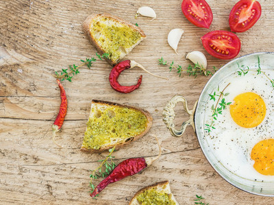 Breakfast set with roasted eggs  bread toasts with pesto souce
