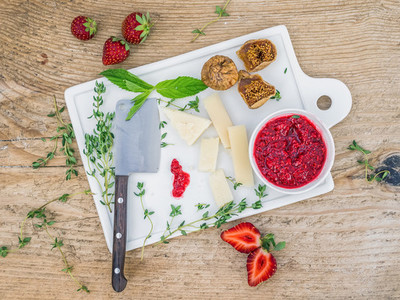 Cheese and fruit set on a white ceramic cutting board