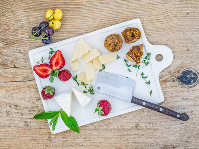 Cheese and fruit set on a wooden desk