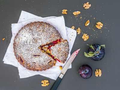 Plum cake with walnuts on a piece of white paper on black