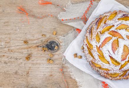 Peach pie with sugar powder over a linen table cloth