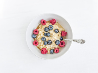 Oat porridge with fresh raspberry blueberry and honey in a whit