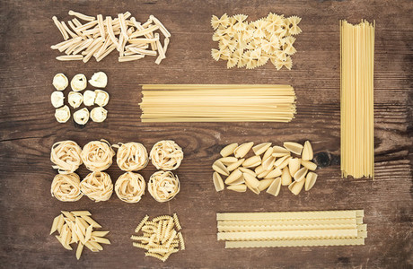 Different types of Italian uncooked pasta on rustic wooden table background  top view