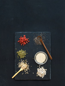Superfoods on black chalkboard background  goji berries  chia  mung beans  buckwheat  quinoa  sunflower seeds  Top view  space for lettering