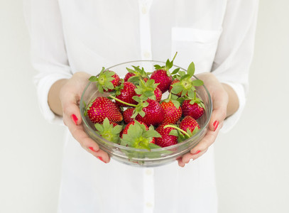 A bowl of strawberries in girl s hands