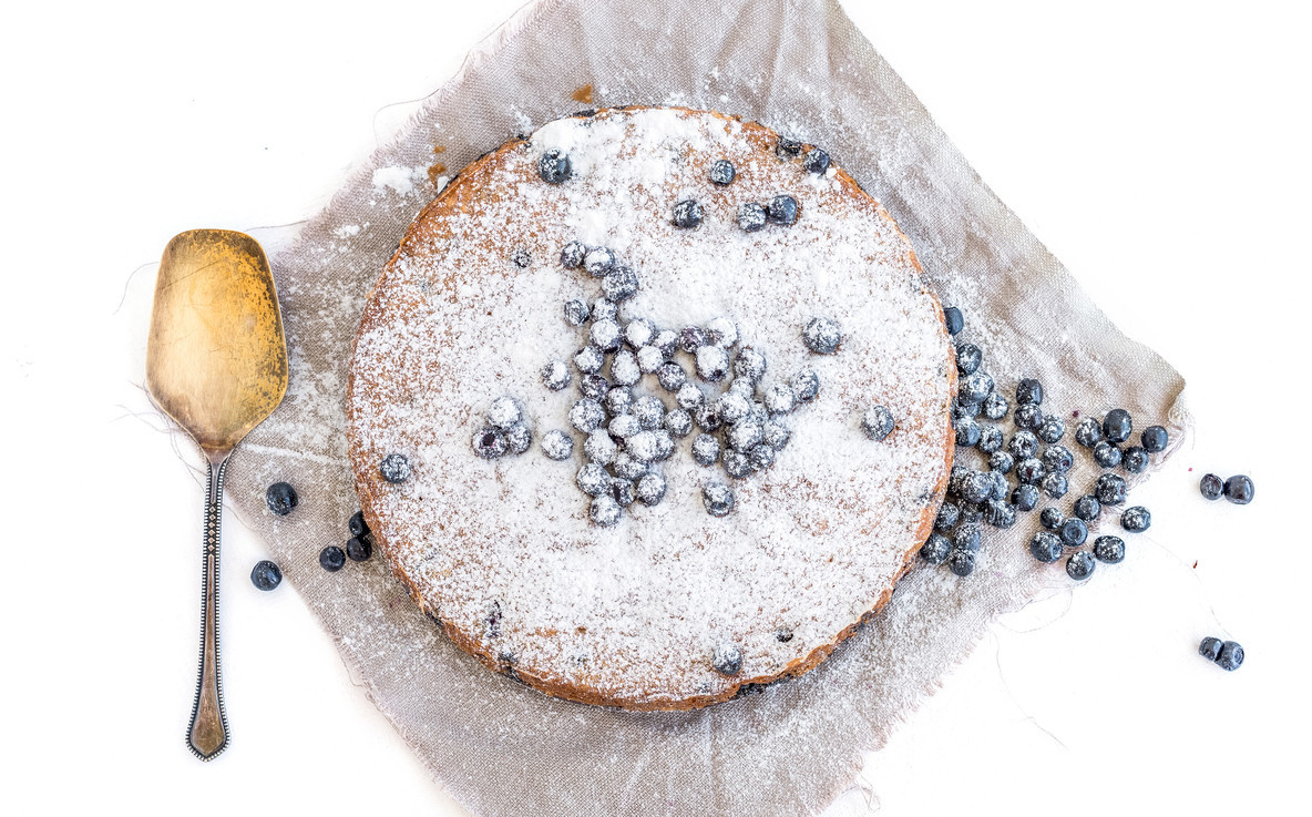 Blueberry cake with fresh bluberries and sugar powder on a beige