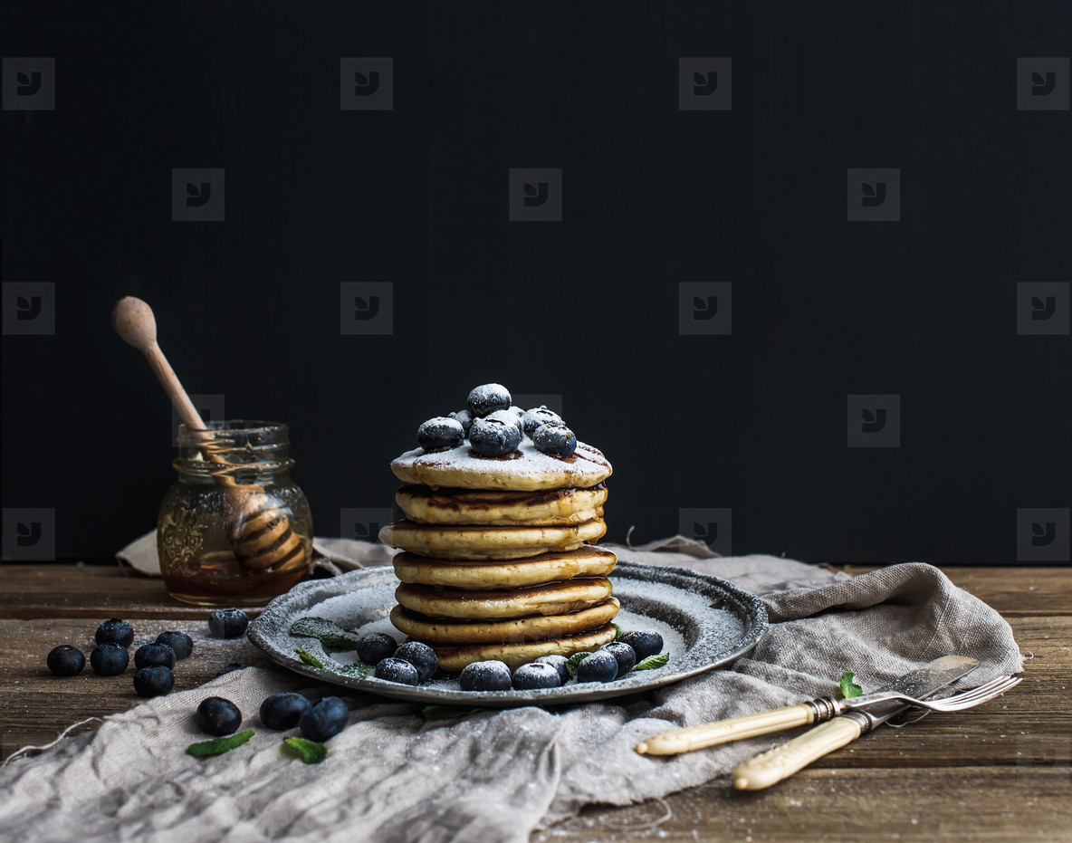 Pancake tower with fresh blueberry and mint on a rustic metal plate