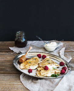 Thin pancakes or crepes with fresh raspberry  cream  mint  on a