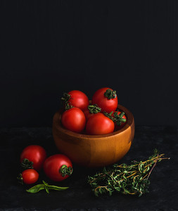 Ripe cherry tomatoes in wooden bowl with basil leaves spices and salt