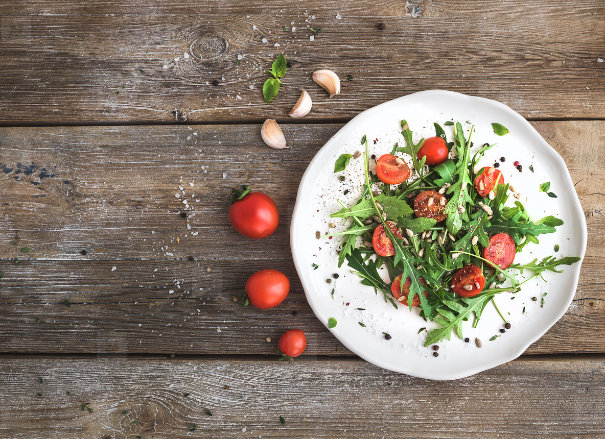 Salad with arugula  cherry tomatoes  sunflower seeds and herbs on white ceramic plate over rustic wood background  top view