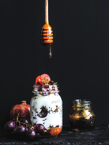 Yogurt and oat granola with grapes  pomegranate  grapefruit in tall glass jar
