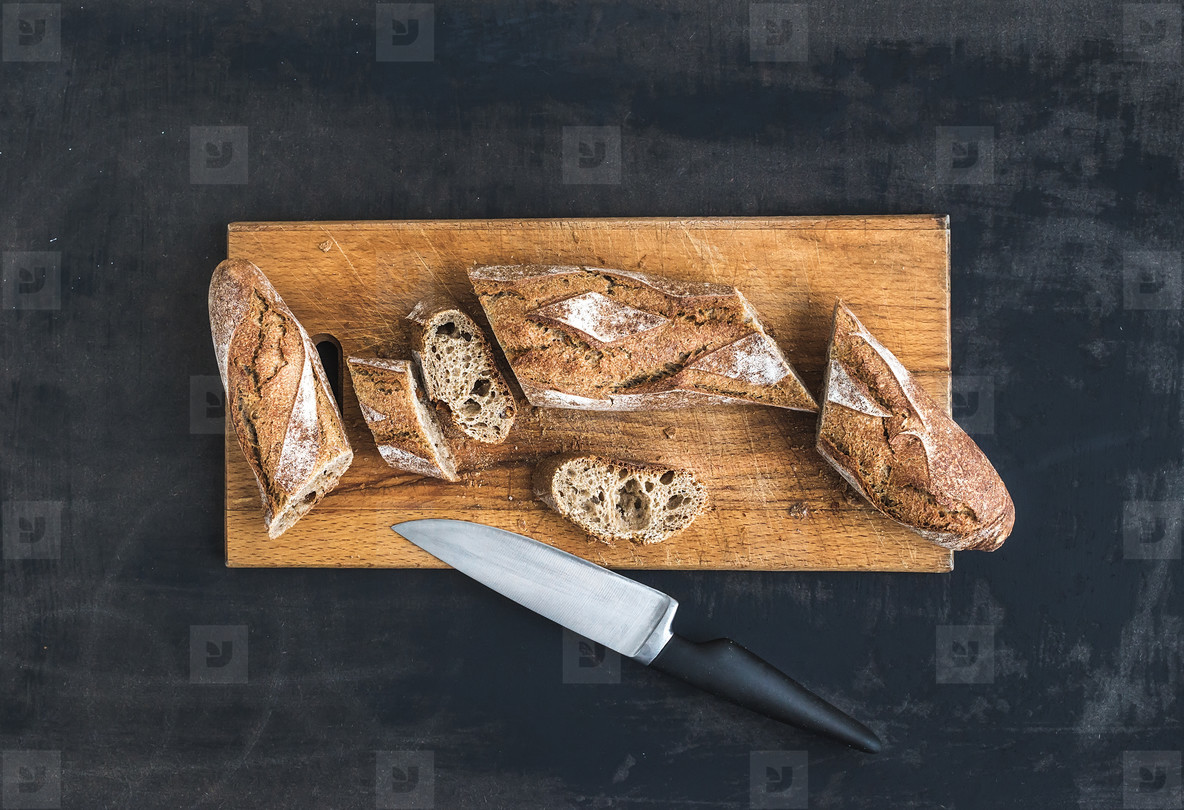 French baguette cut into pieces on a rustic wooden board