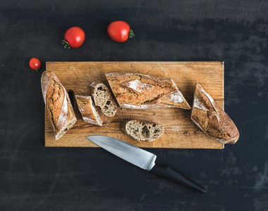 French baguette cut into pieces and cherry tomatoes on a rustic wooden board