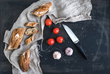 French baguette cut into pieces  cherry tomatoes  garlic and kitchen knife over dark grunge background