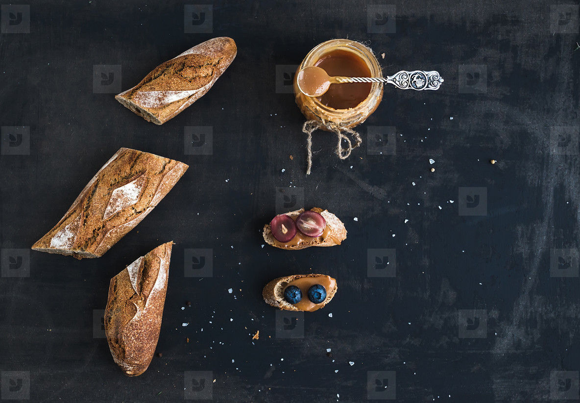 French baguette cut into pieces  sandwiches with red grapes  blueberry and salt caramel sauce on rustic dark background