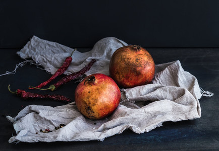 Red ripe pomegranate with spices on dark background