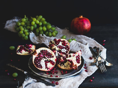 Red ripe peeled pomegranate on rustic metal plate and beige kitchen towel over dark background