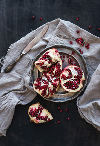 Red ripe peeled pomegranate on rustic metal plate and beige kitchen towel