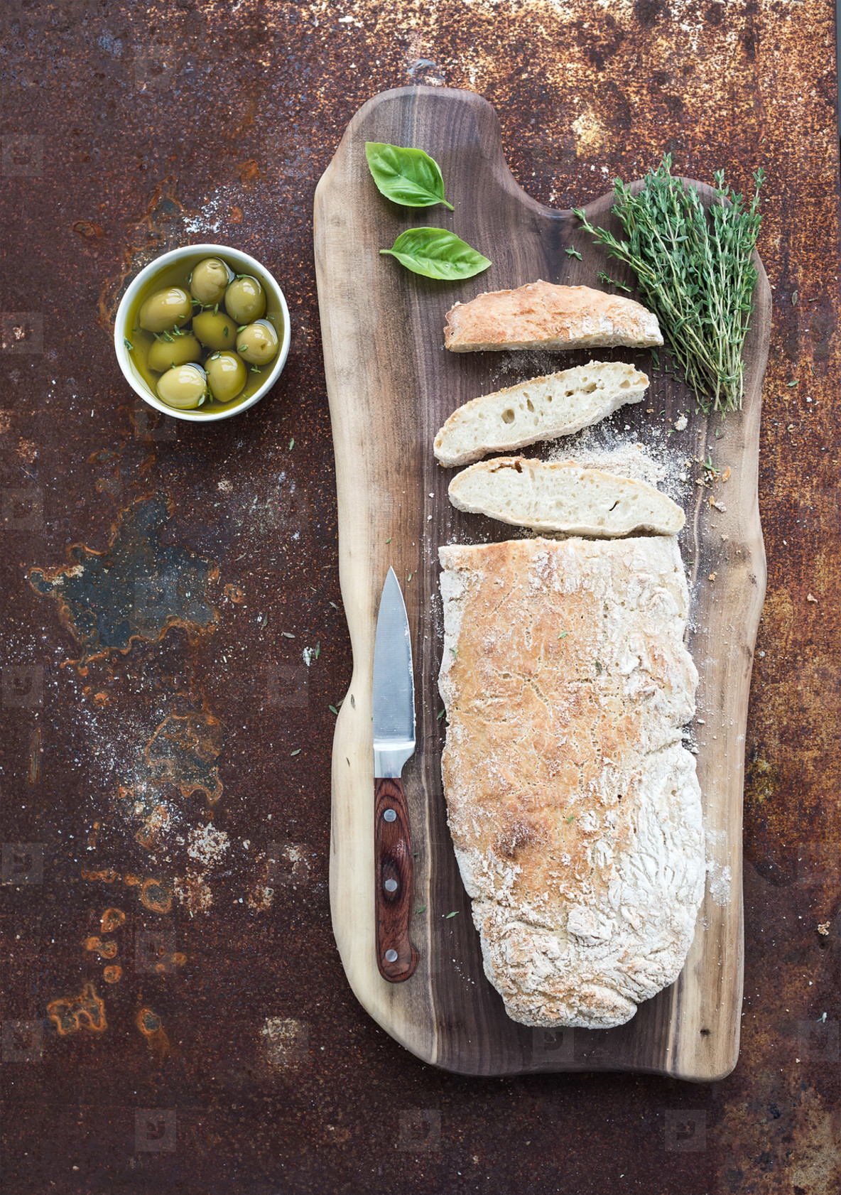 Freshly baked homemade ciabatta bread with olives  basil and thyme on walnut wood board over grunge rusty metal background  top view