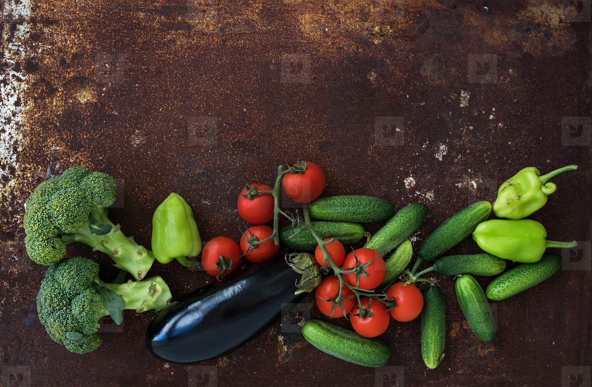Vegetable mix of garden cherry tomatoes  cucumbers  paprikas  eggplant  broccoli on rusty metal grunge background  top view
