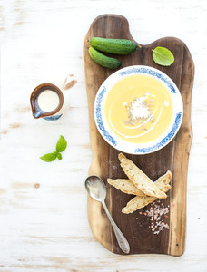 Pumpkin soup with cream  fresh basil  cucumbers and bread in vintage ceramic plate on wooden board over white background  top view