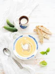 Pumpkin soup with cream  fresh basil  cucumbers and bread in vintage ceramic plate over white wooden background  top view