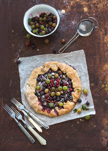 Summer crostata or galette pie with fresh garden berries and vanilla ice cream over grunge rusty metal background  top view