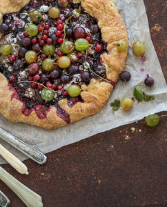 Crostata or galette pie with fresh garden berries over grunge rusty metal background  top view